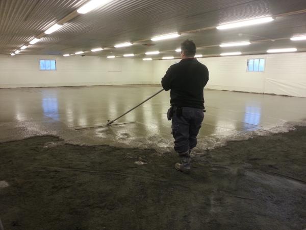 Tungt jobb att skrapa den blöta betongen slät